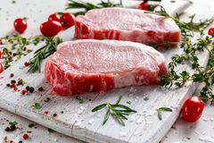 Raw Pork Loin chops on a cutting board with herbs, rosemary, thyme, chilli, salt, pepper on white cutting board. Stock Photos