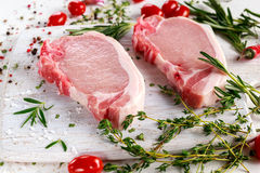 Raw Pork Loin chops on a cutting board with herbs, rosemary, thyme, chilli, salt, pepper on white cutting board. Royalty Free Stock Photos
