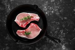 Raw Pork Loin chops in rustic skillet, pan with rosemary. top view. background.  Royalty Free Stock Photography