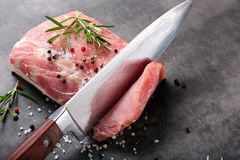 Raw pork loin with spices. And cuting knife Stock Image