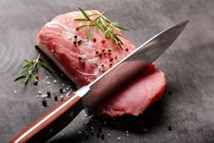 Raw pork loin with spices. And cuting knife Stock Photo