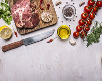 Raw pork in marinade, on a cutting board with tomatoes on a branch, a knife for meat and seasonings border ,place for text on wood Royalty Free Stock Photo