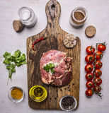 Raw pork in marinade, on a cutting board with tomatoes on a branch, oil, black pepper, herbs on wooden rustic background top view Royalty Free Stock Images