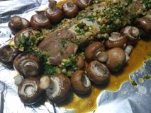 Raw pork marinated on tin foil. With mushrooms, garlic and herbs Stock Images