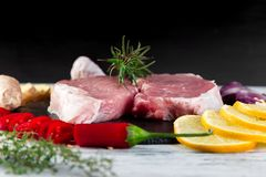Raw pork meat with spice ingredient. Raw pork meat on black slate plate with spice ingredient - rosemary, ginger, chilli pepper, onion Royalty Free Stock Photo