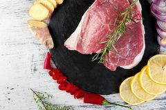 Raw pork meat with spice ingredient. Raw pork meat on black slate plate with spice ingredient - rosemary, ginger, chilli pepper, onion.Top view. Flat lay. Copy Stock Photo