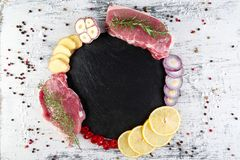 Raw pork meat with spice ingredient. Raw pork meat on black slate plate with spice ingredient - rosemary, ginger, chilli pepper, onion.Top view. Flat lay. Copy stock images
