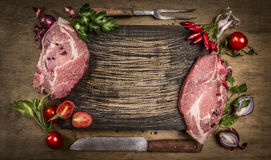 Raw pork meat chops with kitchen tools, fresh seasoning and ingredients for cooking on rustic wooden background, top view, frame.