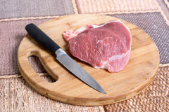 Raw pork meat on the cutting board with knife.  Royalty Free Stock Image