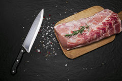 Raw pork meat on a cutting board with rosemary and spices. Raw meat. Raw pork meat on a cutting board with rosemary and spices on black background Royalty Free Stock Photo
