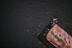 Raw pork meat on a cutting board with rosemary and spices. Raw meat. Raw pork meat on a cutting board with rosemary and spices on black background Royalty Free Stock Images
