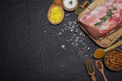 Raw pork meat on a cutting board with rosemary and spices. Raw meat. Raw pork meat on a cutting board with rosemary and spices on black background Stock Images