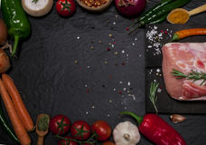 Raw pork meat on a cutting board with rosemary, vegetables and spices. Raw meat. Raw pork meat on a cutting board with rosemary, vegetables and spices on black Stock Image