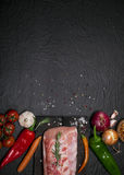 Raw pork meat on a cutting board with rosemary, vegetables and spices. Raw meat. Raw pork meat on a cutting board with rosemary, vegetables and spices on black Stock Photo
