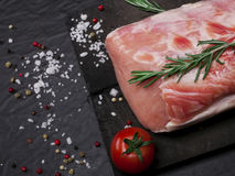 Raw pork meat on a cutting board with rosemary, vegetables and spices. Raw meat. Raw pork meat on a cutting board with rosemary, vegetables and spices on black Royalty Free Stock Photo