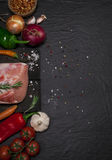 Raw pork meat on a cutting board with rosemary, vegetables and spices. Raw meat. Raw pork meat on a cutting board with rosemary, vegetables and spices on black Royalty Free Stock Images