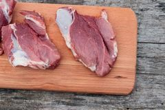 Raw pork meat on cutting board on a table. Top view. Raw pork meat on cutting board on rustic  table. Top view Stock Image