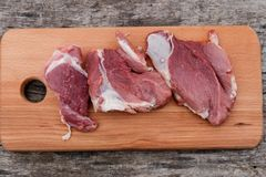 Raw pork meat on cutting board on a table. Top view. Raw pork meat on cutting board on rustic  table. Top view Stock Photos