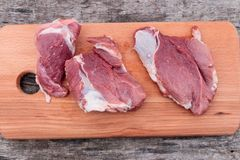 Raw pork meat on cutting board on a table. Top view. Raw pork meat on cutting board on rustic  table. Top view Royalty Free Stock Photo