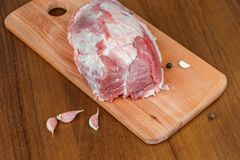 Raw pork meat on cutting board on table. Raw pork meat on cutting board on a table Royalty Free Stock Image
