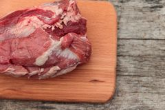 Raw pork meat on cutting board on a table. Top view. Raw pork meat on cutting board on rustic  table. Top view Royalty Free Stock Photography