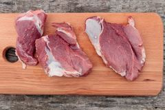 Raw pork meat on cutting board on a table. Top view. Raw pork meat on cutting board on rustic  table. Top view Royalty Free Stock Images
