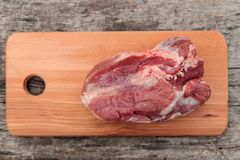 Raw pork meat on cutting board on a table. Top view. Raw pork meat on cutting board on rustic  table. Top view Royalty Free Stock Image
