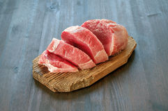 Raw pork meat on cutting board. Cutting board with raw pork meat on wood table Stock Photos