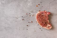 Raw pork meat on a dark gray surface and ingredients for cooking. Food background with copy space royalty free stock image