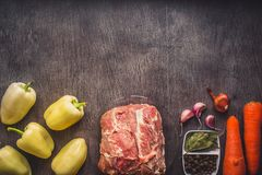Raw pork meat on a dark wooden surface and ingredients for cooking. Food background with copy space. Toned. Raw pork meat on a dark wooden surface and Royalty Free Stock Photo