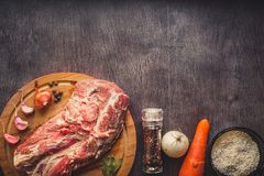 Raw pork meat on a dark wooden surface and ingredients for cooking. Food background with copy space. Toned. Raw pork meat on a dark wooden surface and Royalty Free Stock Photography