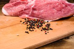 Raw pork meat and different spiceson cutting board. Raw pork meat and different spices on wooden cutting board Stock Images