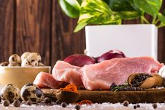Raw pork meat with few spices and eggs. Horizontal photo with few slices of raw pork meat on wooden plate with spice as pepper or paprika around together with Stock Images