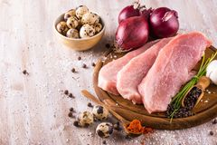 Raw pork meat with few spices and quail eggs. Horizontal photo with few slices of raw pork meat on wooden plate with spice as pepper or paprika around together Royalty Free Stock Images