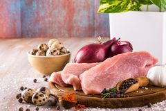 Raw pork meat with few spices and vegetable. Horizontal photo with few slices of raw pork meat on wooden plate with spice as pepper or paprika around together Stock Image
