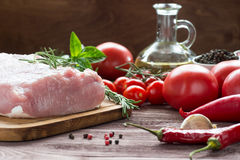Raw pork meat with freash vegetables. Raw pork meat on a dark wooden surface and ingredients for cooking. Food background Stock Photo