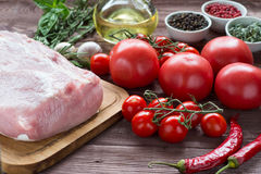 Raw pork meat with freash vegetables. Raw pork meat on a dark wooden surface and ingredients for cooking. Food background Stock Photos