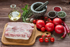 Raw pork meat with freash vegetables. Raw pork meat on a dark wooden surface and ingredients for cooking. Food background Stock Image