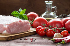 Raw pork meat with freash vegetables. Raw pork meat on a dark wooden surface and ingredients for cooking. Food background Stock Photography