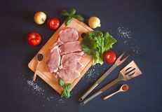 Raw pork meat. Fresh steaks on cutting board. With vegetables and seasonings on dark background. Top view Stock Photography