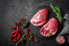 Raw pork meat. Fresh steaks on slate board on black background. Top view stock images
