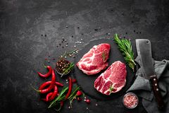 Raw pork meat. Fresh steaks on slate board on black background. Top view Stock Photography