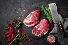 Raw pork meat. Fresh steaks on slate board on black background. Top view Royalty Free Stock Images