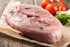 Raw pork meat and fresh vegetables. On wooden table Stock Photo