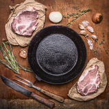 Raw pork meat with ingredients for cooking around cast-iron frying pan with knife for meat  meat fork on rustic wooden backgrou Stock Photo