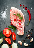 Raw pork meat and ingredients. Raw pork meat on a dark gray surface and ingredients for cooking. Food background Stock Photo