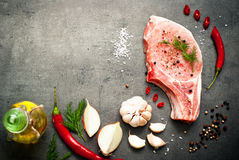 Raw pork meat and ingredients. Raw pork meat on a dark gray surface and ingredients for cooking. Food background with copy space Royalty Free Stock Photo