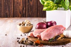 Raw pork meat with several spices and vegetable. Horizontal photo with few slices of raw pork meat on wooden plate with spice as pepper or paprika around Stock Image