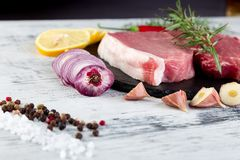Raw pork meat with spice ingredient. Raw pork meat on black slate plate with spice ingredient - rosemary, ginger, chilli pepper, onion Stock Photos