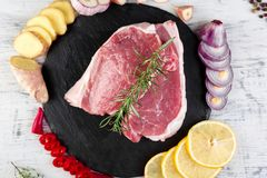Raw pork meat with spice ingredient. Raw pork meat on black slate plate with spice ingredient - rosemary, ginger, chilli pepper, onion.Top view. Flat lay. Copy Royalty Free Stock Photography